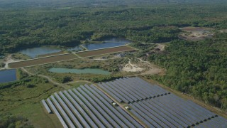 AX144_213 - 6k stock footage aerial video flying by solar array, ponds, dense trees, Dartmouth, Massachusetts
