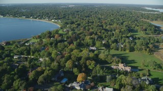 AX145_017 - 6k stock footage aerial video flying over homes near the shore, colorful trees, Barrington, Rhode Island