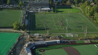AX145_065 - 6k stock footage aerial video approaching a football practice, tilt down, Brown University, Providence, Rhode Island