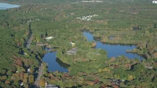 AX145_099 - 6k stock footage aerial video flying by Orrs Pond, waterfront property, forest, autumn, Attleboro, Massachusetts