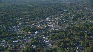 AX145_103 - 6k stock footage aerial video flying by small town center, trees, autumn, North Attleborough, Massachusetts