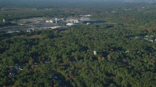 AX145_110 - 6k stock footage aerial video flying by Gillette Stadium, dense trees, autumn, Foxborough, Massachusetts