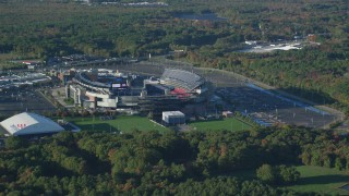 AX145_111 - 6k stock footage aerial video flying away from Gillette Stadium, trees, autumn, Foxborough, Massachusetts