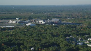 AX145_112 - 6k stock footage aerial video flying by Gillette Stadium, dense trees, autumn, Foxborough, Massachusetts