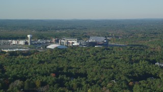 AX145_113 - 6k stock footage aerial video flying by Gillette Stadium, dense trees, autumn, Foxborough, Massachusetts