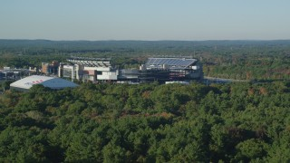 AX145_115 - 6k stock footage aerial video flying low over trees, approach Gillette Stadium, autumn, Foxborough, Massachusetts