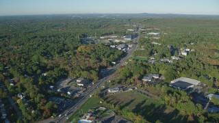 AX145_120 - 6k stock footage aerial video flying over Boston Providence Highway, warehouses, autumn, Walpole, Massachusetts