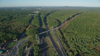 AX145_124 - 6k stock footage aerial video approaching Interstate 95, deciduous forests, autumn, Walpole, Massachusetts