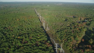 AX145_126 - 6k stock footage aerial video flying by decision forest, power lines, autumn, Walpole, Massachusetts