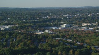 AX145_127 - 6k stock footage aerial video flying by office buildings, colorful trees, autumn, Norwood, Massachusetts