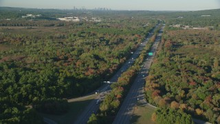 AX145_130 - 6k stock footage aerial video flying by Interstate 95, colorful trees in autumn, Norwood, Massachusetts