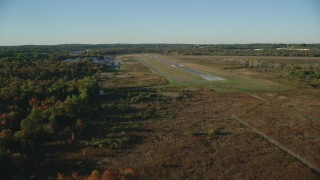AX145_131 - 6k stock footage aerial video flying by trees, autumn, approach the Norwood Memorial Airport, Massachusetts