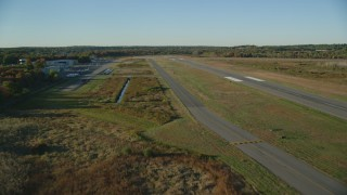 AX145_132 - 6k stock footage aerial video flying over small airport in autumn, Norwood Memorial Airport, Massachusetts