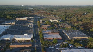 AX146_001 - 6k stock footage aerial video flying by office buildings, warehouses, autumn, Westwood, Massachusetts, sunset