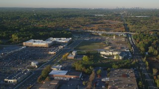 AX146_002 - 6k stock footage aerial video flying by office building, dense trees, autumn, Westwood, Massachusetts, sunset