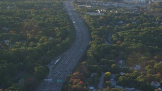 AX146_004 - 6k stock footage aerial video flying by interstate 93, heavy traffic, autumn, Westwood, Massachusetts, sunset