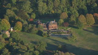 AX146_005 - 6k stock footage aerial video flying by isolated mansion, autumn, Westwood, Massachusetts, sunset