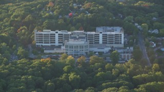 AX146_010 - 6k stock footage aerial video flying by Faulkner Hospital in autumn, Jamaica Plain, Massachusetts, sunset
