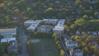 AX146_013 - 6k stock footage aerial video flying by Brookline High School, Brookline, Massachusetts, sunset