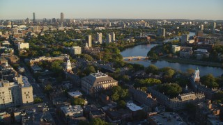 AX146_021 - 6k stock footage aerial video orbiting Harvard University, reveal Charles River, Cambridge, Massachusetts, sunset