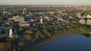 AX146_030 - 6k stock footage aerial video orbiting Harvard University, Cambridge, Massachusetts, sunset