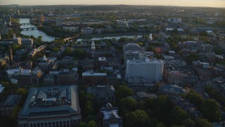 AX146_037 - 6k stock footage aerial video flying over Harvard University, approaching Charles River, Massachusetts, sunset