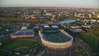 AX146_041 - 6k stock footage aerial video approaching Harvard Stadium, Harvard University, Massachusetts, sunset