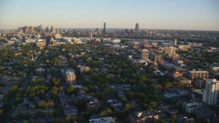 AX146_046 - 6k stock footage aerial video flying by neighborhoods, Downtown Boston skyline, Cambridge, Massachusetts, sunset