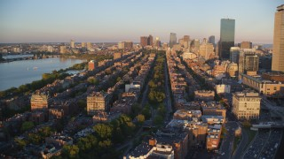 AX146_062 - 6k stock footage aerial video flying over Back Bay, approaching Downtown Boston, Massachusetts, sunset
