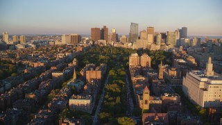 AX146_064 - 6k stock footage aerial video approaching Boston Common, Downtown Boston, Massachusetts, sunset
