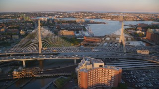 AX146_072 - 6k stock footage aerial video flying over Zakim Bridge, reveal Constitution Marina, Boston, Massachusetts, sunset