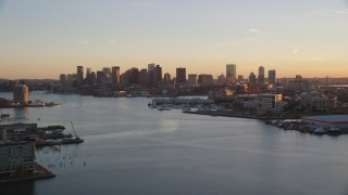 AX146_076 - 6k stock footage aerial video flying over Charles River, approach skyline, Downtown Boston, Massachusetts, sunset