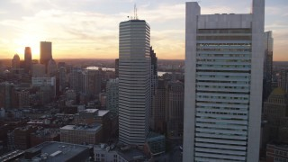 AX146_084 - 6k stock footage aerial video flying by skyscrapers, Downtown Boston, Massachusetts, sunset
