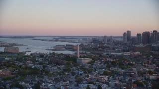 AX146_093 - 6k stock footage aerial video flying by Bunker Hill Monument, downtown skyline, Charlestown, Massachusetts, sunset