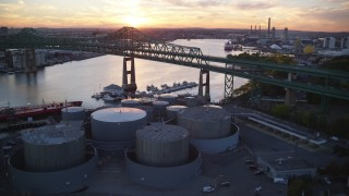 AX146_099 - 6k stock footage aerial video flying over storage tanks, approach Tobin Memorial Bridge, Chelsea, Massachusetts, sunset