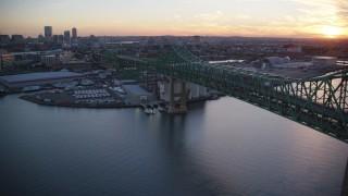 AX146_100 - 6k stock footage aerial video panning by Tobin Memorial Bridge, reveal downtown, Charlestown, Massachusetts, sunset