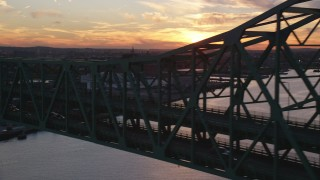 AX146_105 - 6k stock footage aerial video flying by the Tobin Memorial Bridge, Charlestown, Massachusetts, sunset