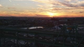 AX146_107 - 6k stock footage aerial video flying by the Tobin Memorial Bridge, Charlestown, Massachusetts, sunset