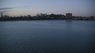 AX146_119 - 6k stock footage aerial video flying by waterfront homes, approach apartments, South Boston, Massachusetts, twilight