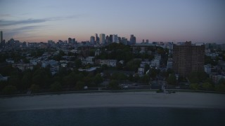 AX146_120 - 6k stock footage aerial video of Waterfront homes, Dorchester Heights Monument, South Boston, Massachusetts, twilight