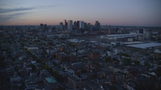 AX146_122 - 6k stock footage aerial video approaching downtown skyline, South Boston, Massachusetts, twilight