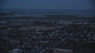 AX146_131 - 6k stock footage aerial video flying by Logan International Airport, Boston, Massachusetts, twilight