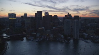 AX146_135 - 6k stock footage aerial video flying by Rowes Wharf, skyline, Downtown Boston, Massachusetts, twilight