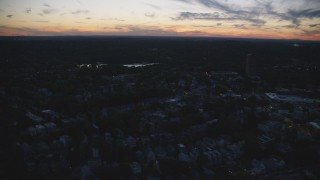 AX146_151 - 6k stock footage aerial video flying by neighborhood, Jamaica Pond, Jamaica Plain, Massachusetts, twilight