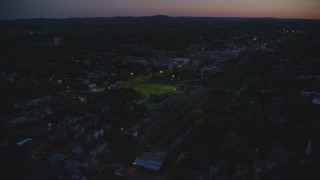 AX146_152 - 6k stock footage aerial video flying by sports fields, tilt down, Jamaica Plain, Massachusetts, twilight
