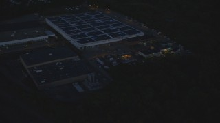 AX146_162 - 6k stock footage aerial video flying away from a large warehouse, Hyde Park, Massachusetts, night