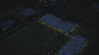AX146_165 - 6k stock footage aerial video flying by a strip mall, Westwood, Massachusetts, night