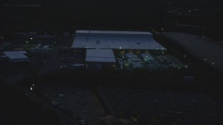 AX146_166 - 6k stock footage aerial video flying by a warehouse, Westwood, Massachusetts, night