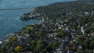 AX147_027 - 6k stock footage aerial video flying over a coastal community with trees along the harbor, Marblehead, Massachusetts