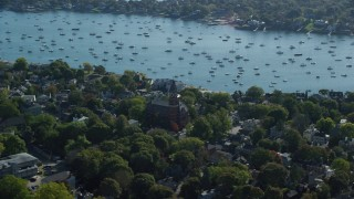 AX147_029 - 6k stock footage aerial video orbiting Abbott Hall among trees along the harbor, Marblehead, Massachusetts